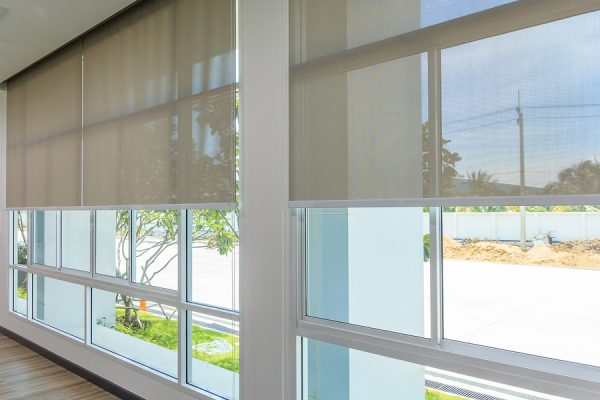 Motorized shades on large banks of windows along a hallway with road and landscaping visible on the outside of the windows.