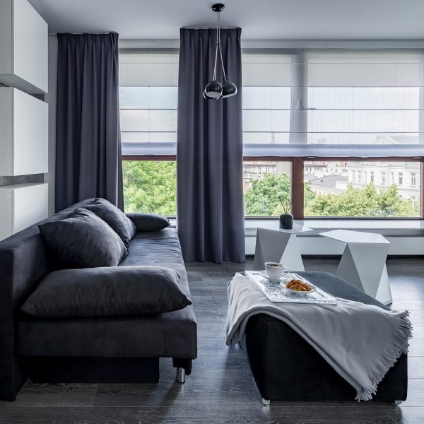 Large gray couch with ottoman and food tray, long gray curtains to match and white shades.
